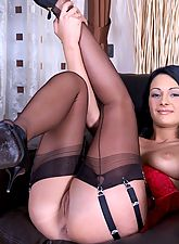 Black-haired new model in sexy black stiletto shoes, sheer black thigh-high stockings, and red lace corset